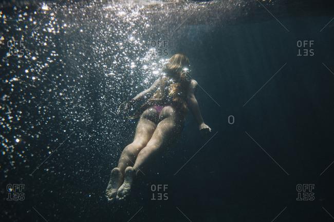 Rear view of woman swimming undersea