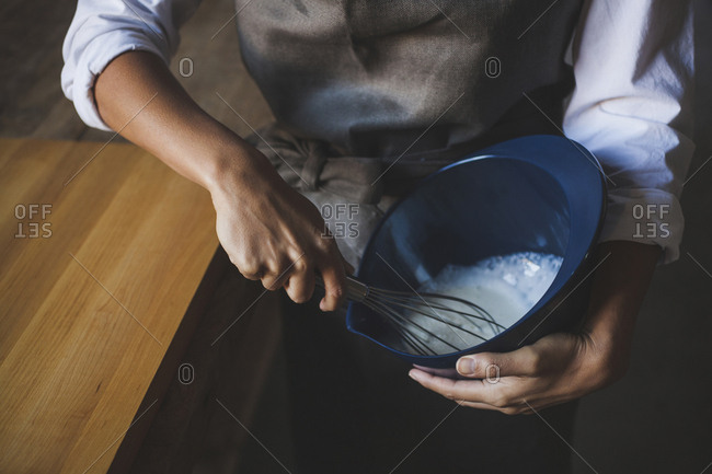 Midsection of woman whisking batter in bowl while standing by table