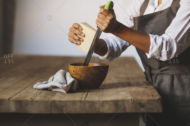 Midsection of woman grating cheese in bowl while standing by wooden table