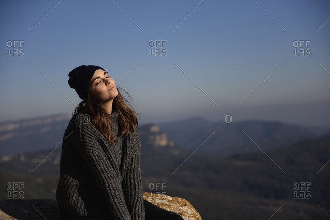 Woman with eyes closed sitting on cliff against sky
