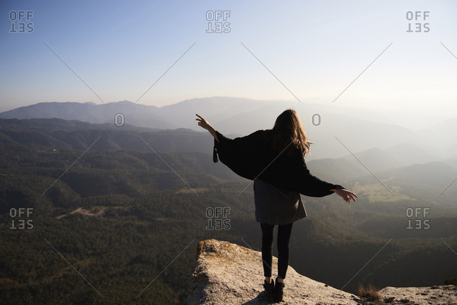 Rear view of woman gesturing while standing on cliff against mountains