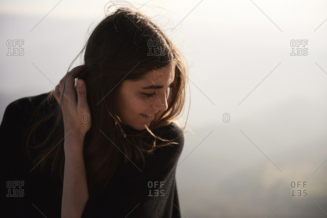 Woman with hand in hair against sky