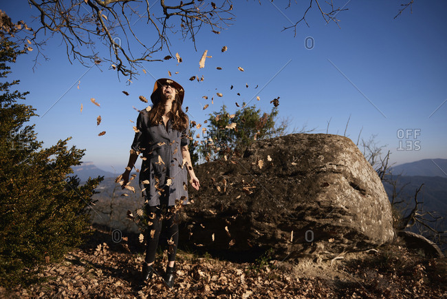 Happy woman playing with leaves while standing on cliff against clear blue sky