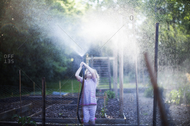 Girl playing with playing with garden hose