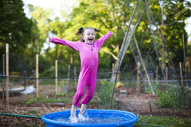 Cheerful girl jumping in wading pool on field