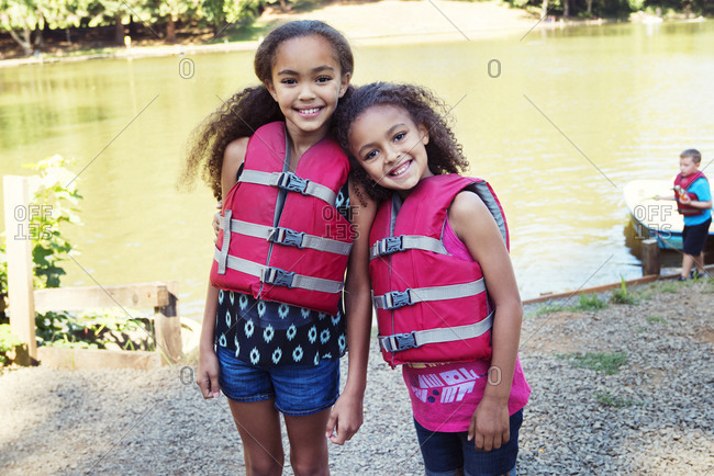 Portrait of girls wearing life jackets while standing at lakeshore