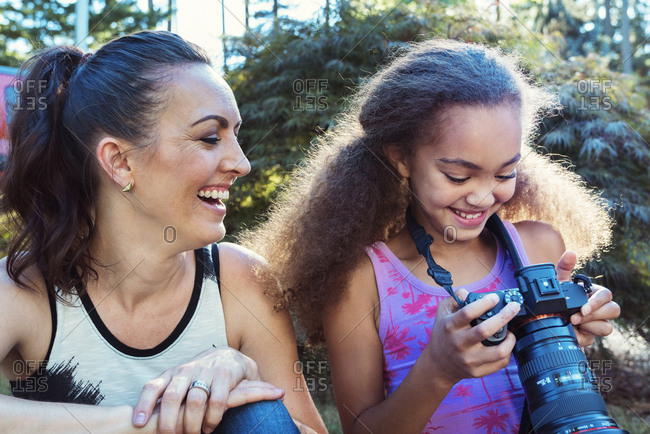 Happy mother and daughter looking at digital camera while sitting in yard
