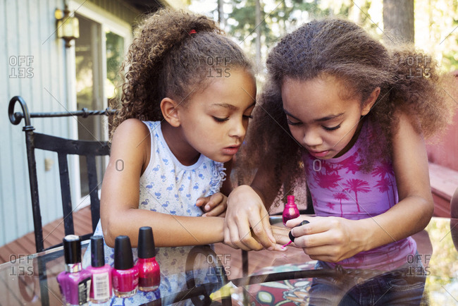 Girl applying nail polish on sister's fingernails while sitting at table in yard