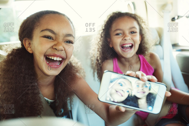 Happy girl showing photograph in smart phone while traveling with sister