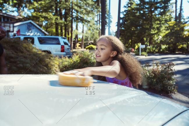 Girl washing car in driveway