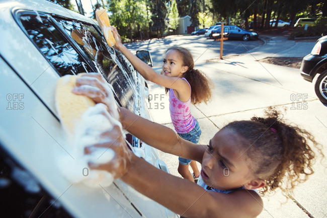 High angle view of girls washing car in driveway