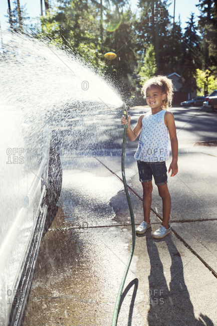 Girl spraying water on car in driveway