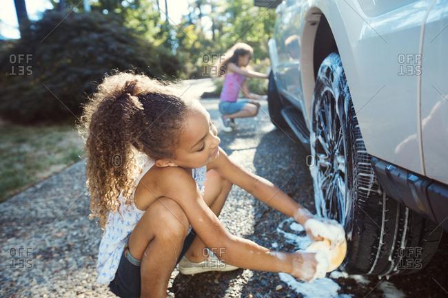 Girls washing car in driveway