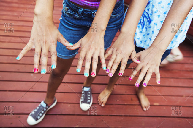 Low section of girls showing nail polish on fingernails while standing in yard