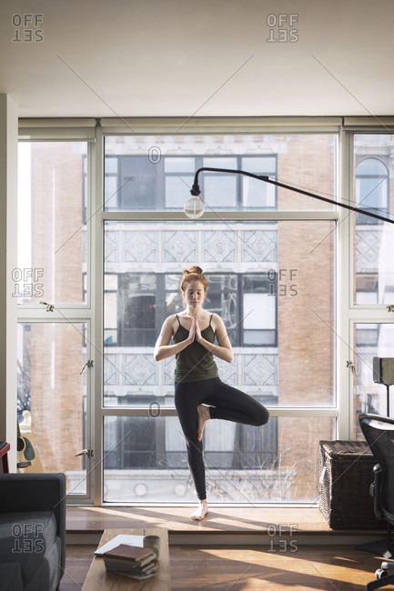 Woman practicing tree pose by window at home