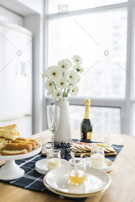 Food and drinks with flower vase arranged on dining table at home