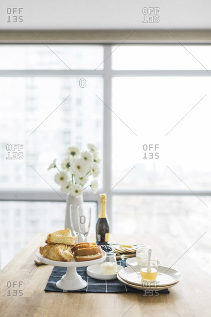 Food and drinks with flower vase arranged on dining table by window at home