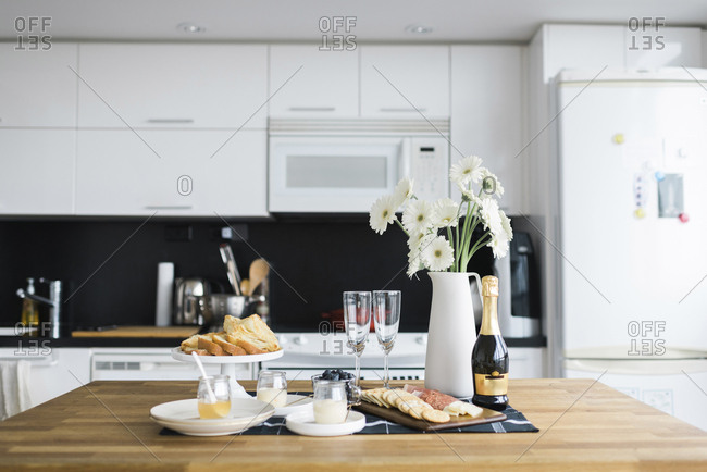 Food and drinks with flower vase arranged on table in kitchen