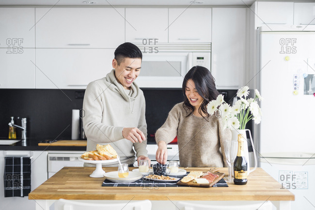 Happy couple having breakfast while standing at dining table in kitchen