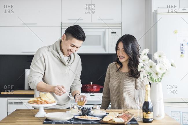 Woman looking at boyfriend preparing breakfast in kitchen