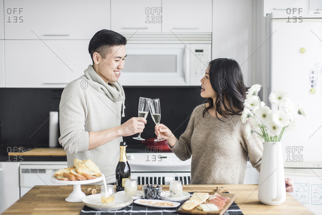 Happy couple toasting Prosecco in kitchen at home