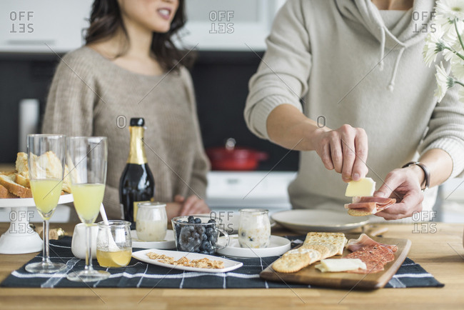 Midsection of man making breakfast with girlfriend in kitchen