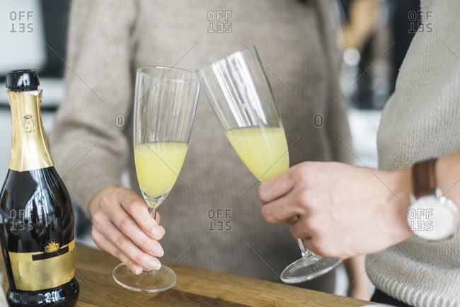 Midsection of couple toasting drinks at table in kitchen