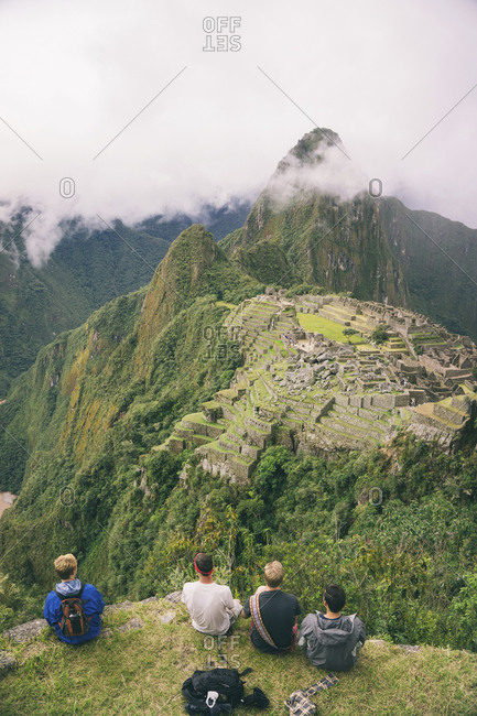 Rear view of friends sitting on mountain against Machu Picchu