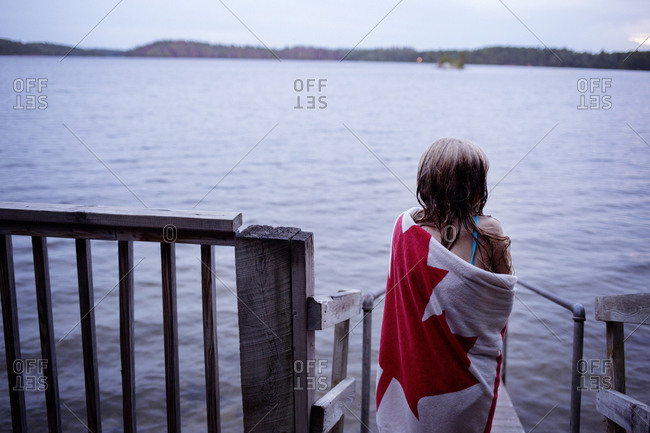 Rear view of girl wrapped in towel standing on jetty over lake
