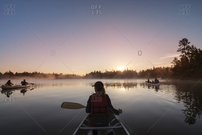 Rear view of woman traveling in boat on calm lake against blue sky