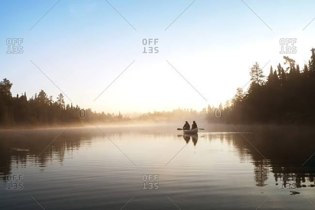 People traveling in boat on lake against sky during foggy weather