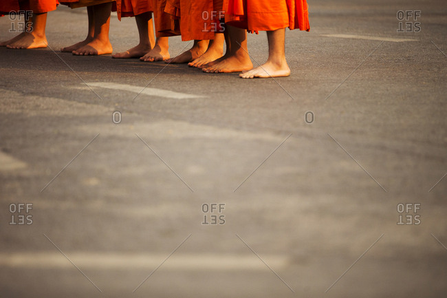 Cropped image of monks standing on road