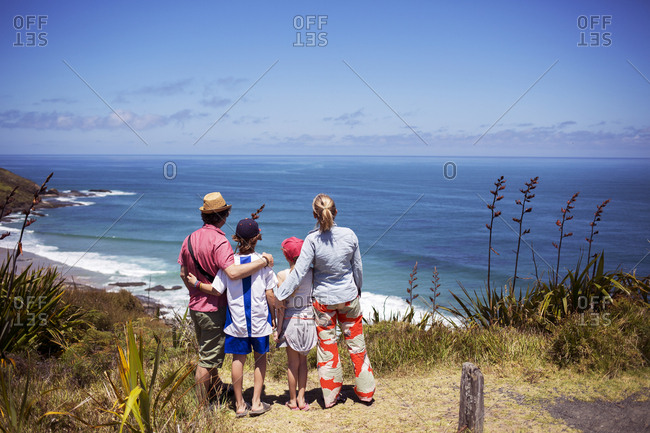 Rear view of family standing on hill and looking at sea against sky