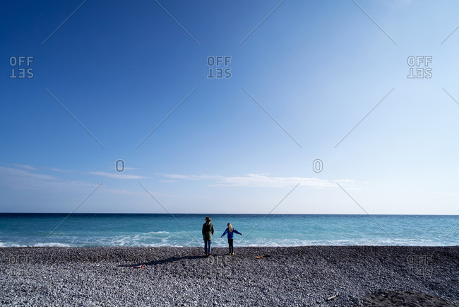 Rear view of senior woman standing with girl at beach against sky