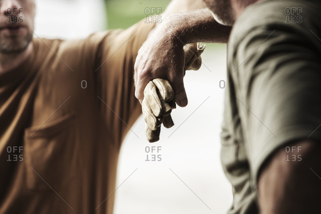Cropped image of farm worker holding protective gloves while standing by friend