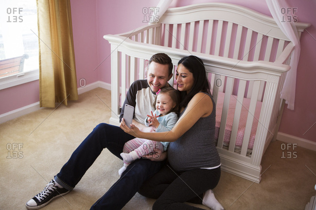 High angle view of family taking selfie while sitting against crib at home