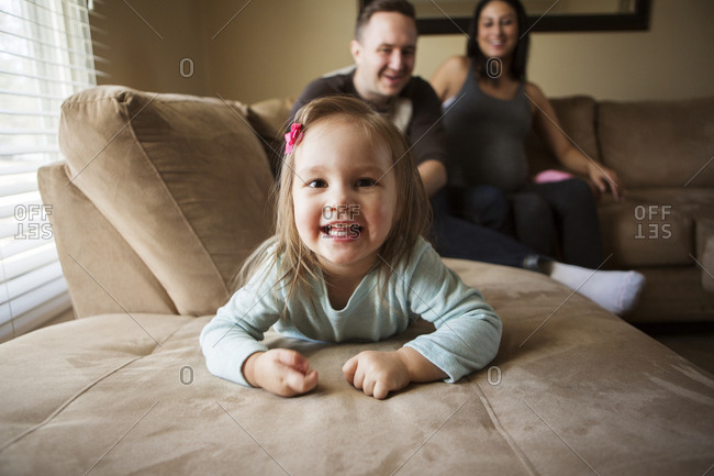 Portrait of cute girl lying while parents sitting on sofa at home