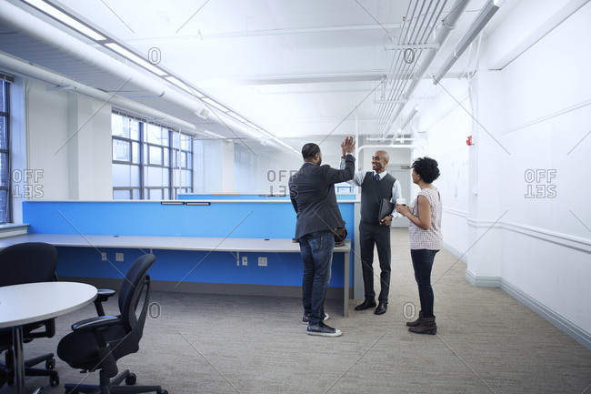 Businessmen high fiving while standing with female colleague in office