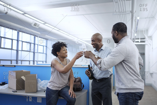 Cheerful business people toasting drinks in office