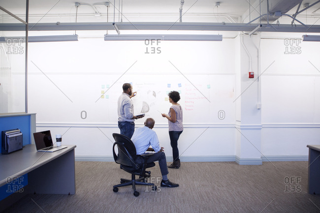 Business people planning while writing on whiteboard in office
