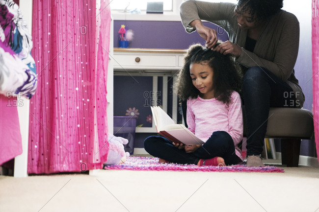 Woman combing daughter's hair at home