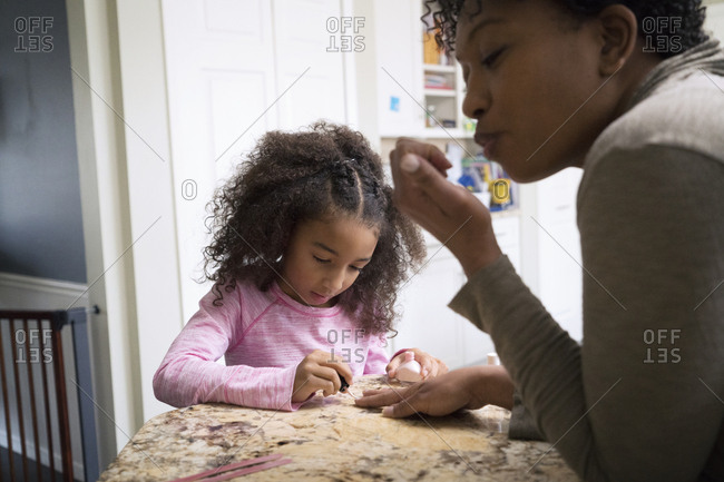 Girl painting mother's fingernails at home