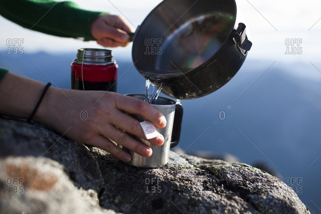 Cropped hands of hiker pouring water in coffee cup