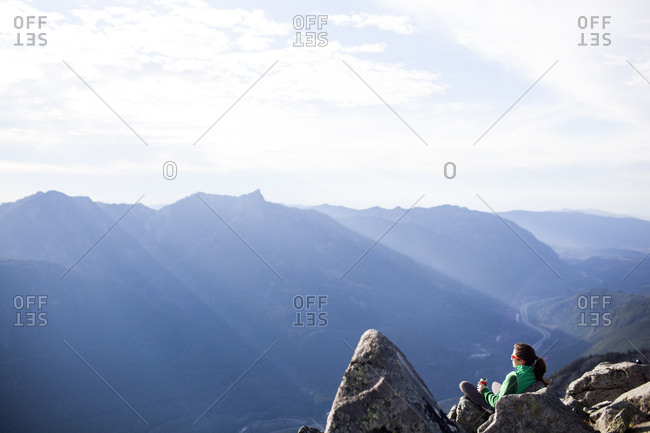 High angle view of woman relaxing on rocks against mountain range