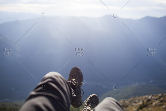 Low section of hiker sitting on cliff against mountains