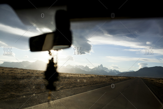 Scenic view clouds over mountains seen through car windshield