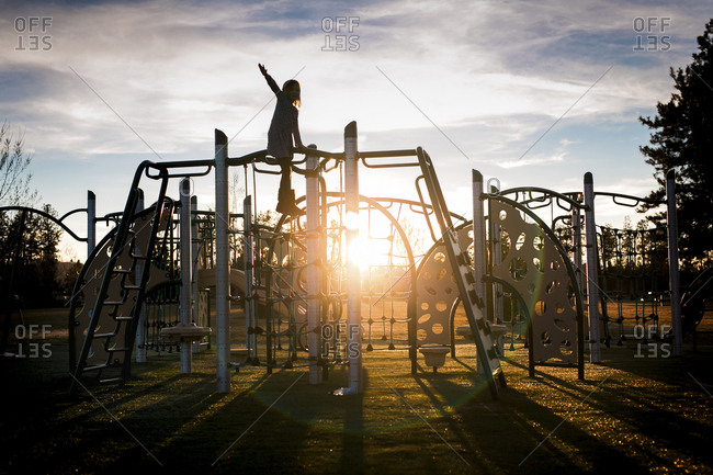 Girl playing on metallic structure at park against cloudy sky