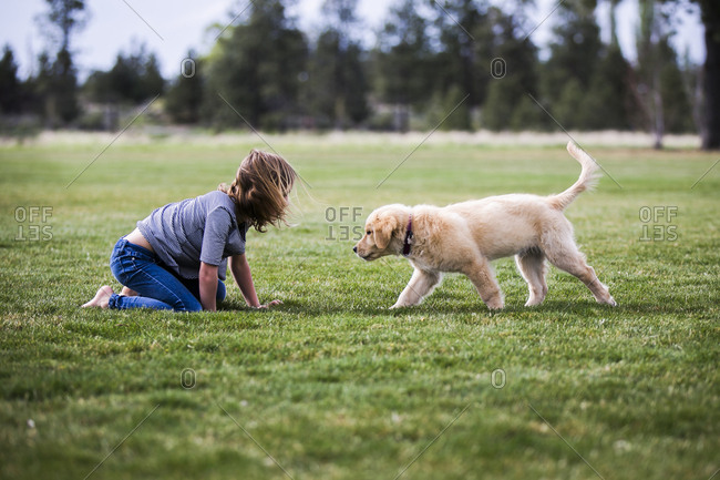 Side view of girl playing with dog on field