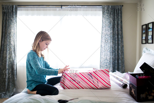 Side view of girl wrapping gift box while kneeling on bed