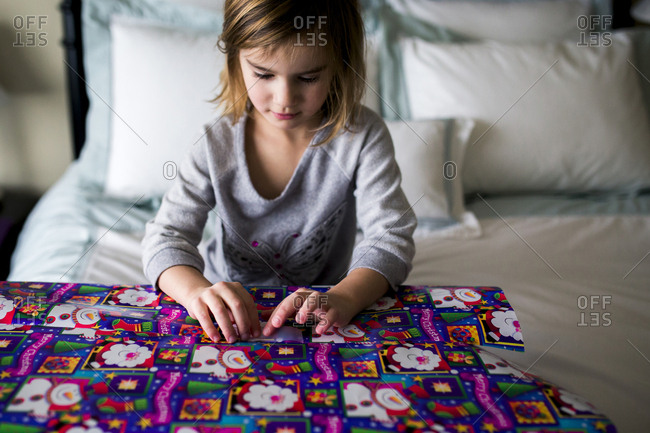 Girl wrapping gift box while sitting on bed